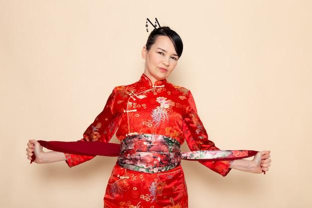 クリーム色の背景のデザインされたベルトでデザインされたベルトでエレガントなポーズをとる伝統的な赤い和服の絶妙な日本の芸者の正面図
