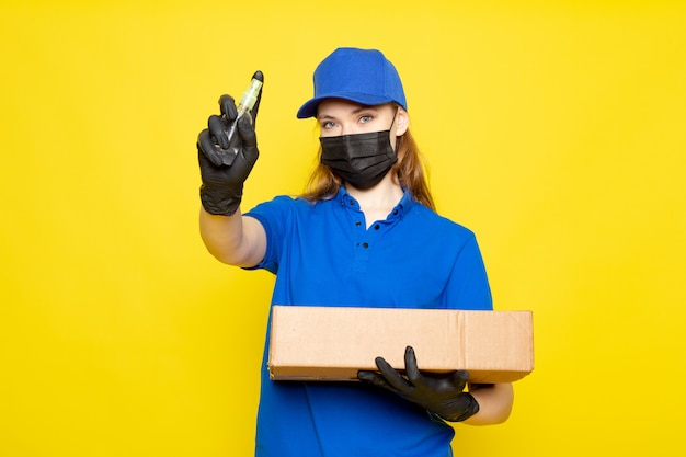 Фронтальный вид женского привлекательного курьера в синей рубашке поло, синей кепке и джинсах с пакетом в черных перчатках, черной защитной маской, держащей спрей на желтом фоне, в службе общественного питания