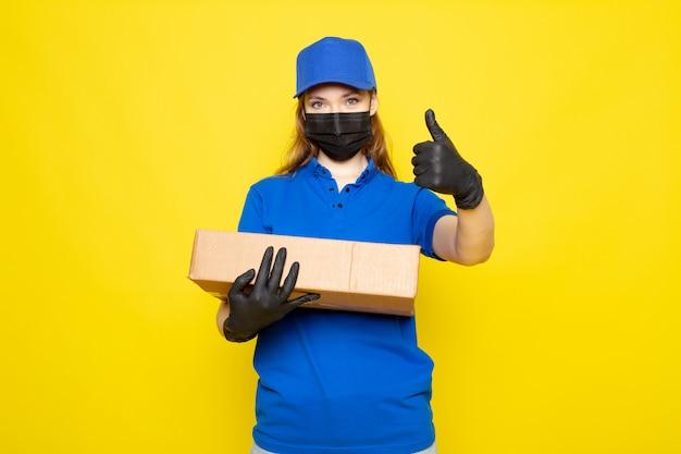 Фронтальный вид женского привлекательного курьера в синей рубашке поло, синей кепке и джинсах с пакетом в черных перчатках, черной защитной маской на желтом фоне, в службе общественного питания