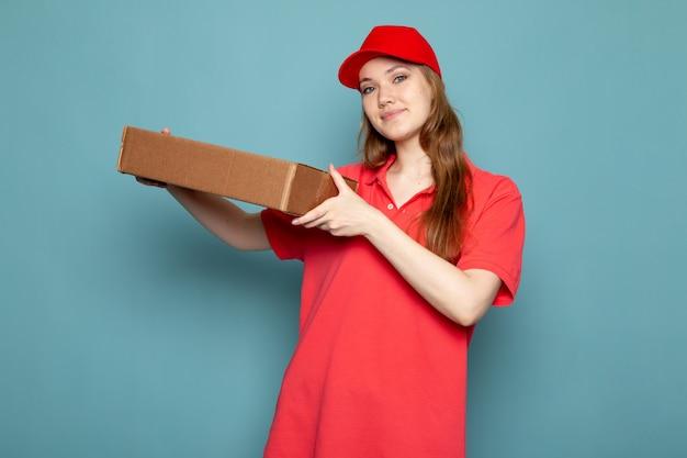 赤いポロシャツの赤い帽子とジーンズが青い背景のフードサービスの仕事でポーズパッケージを保持している正面の女性の魅力的な宅配便