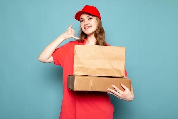 青い背景のフードサービスの仕事に笑みを浮かべて彼女の架空の電話を使用して茶色のパッケージを保持している赤いポロシャツの赤い帽子の正面の女性の魅力的な宅配便