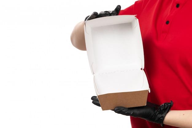 Вид спереди курьер женского пола в красной рубашке и черных перчатках, держа пустой пакет с едой