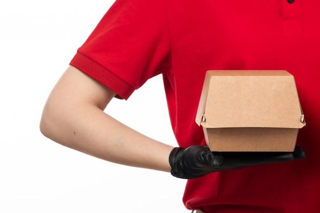 Вид спереди курьер женского пола в красной рубашке и черные перчатки, держа пакет с едой