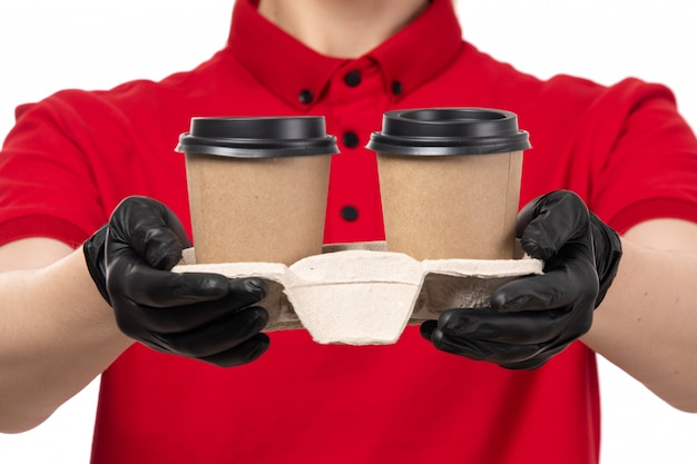 Вид спереди курьер женского пола в красной рубашке черные перчатки, держа кофейные чашки
