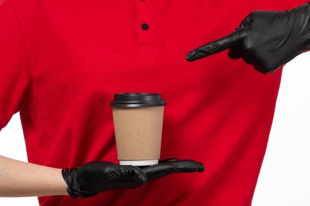 Вид спереди курьер женского пола в красной рубашке черные перчатки, держа кофе на белом