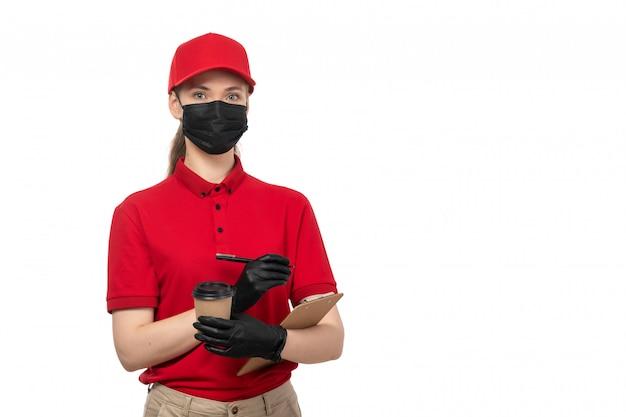 Вид спереди курьер женского пола в красной рубашке, красной шапочке, черных перчатках и черной маске, держа кофе и записывая