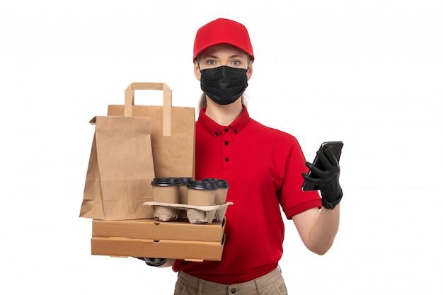 Вид спереди курьер женского пола в красной рубашке, красной кепке, черных перчатках и черной маске с пакетами кофе и смартфон