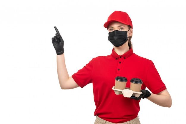 Вид спереди курьер женского пола в красной рубашке, красной шапочке, черных перчатках и черной маске с кофе