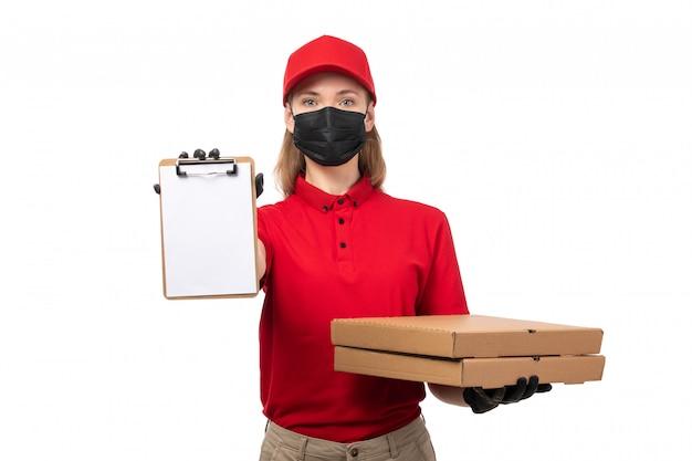 Вид спереди курьер женского пола в красной рубашке, красной кепке, черных перчатках и черной маске с коробками для бумаги и пиццы на белой униформе