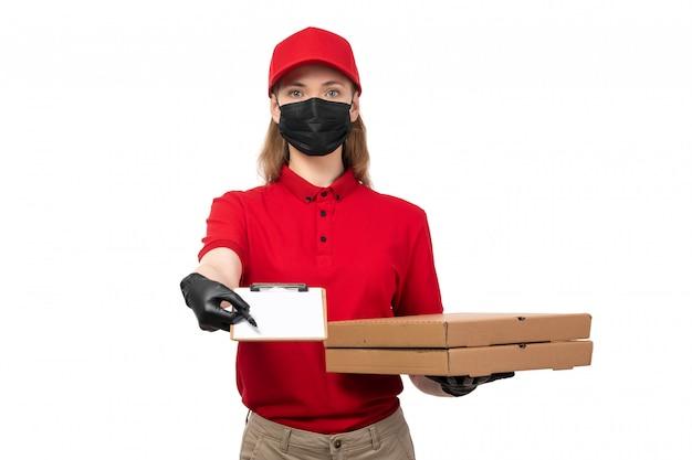 Вид спереди курьерской женщины в красной рубашке, красной кепке, черных перчатках и черной маске с коробками для пиццы и бумагой на белой рабочей форме