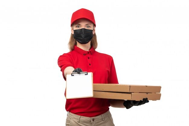 Вид спереди курьер женского пола в красной рубашке, красной шапочке, черных перчатках и черной маске с коробками для пиццы и бумагой на белом