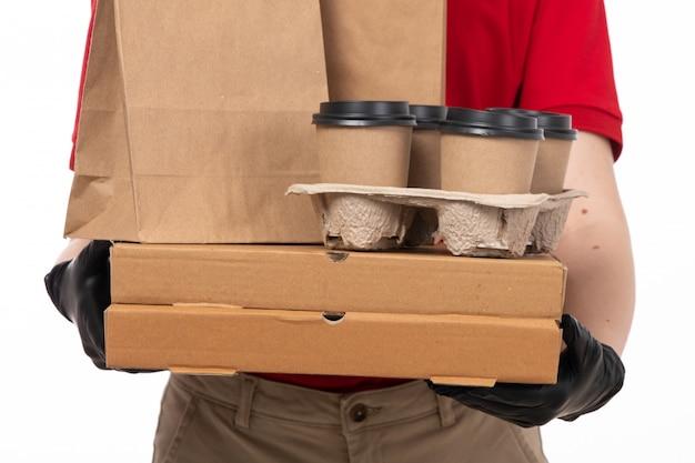Вид спереди курьер женского пола в красной крошке красной шапочке черные перчатки и черная маска, держа пакеты с едой и кофе на белом