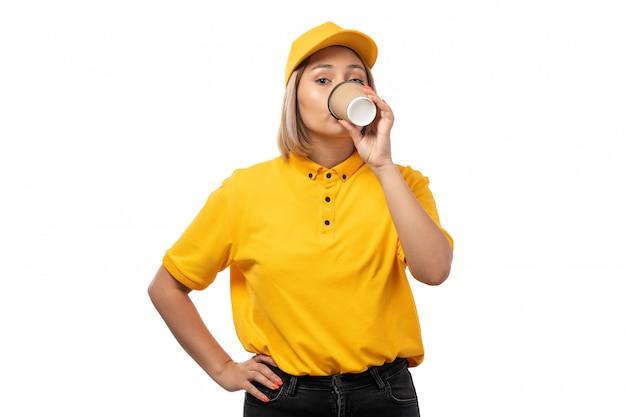 Вид спереди курьер женского пола в желтой рубашке желтой кепке и черных джинсах, пить кофе на белом