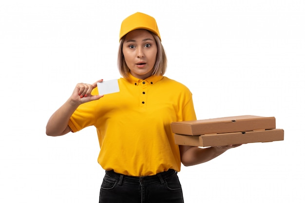 黄色のシャツの黄色い帽子と白い背景のピザをフードにボックスを保持している黒いジーンズの正面図女性宅配便