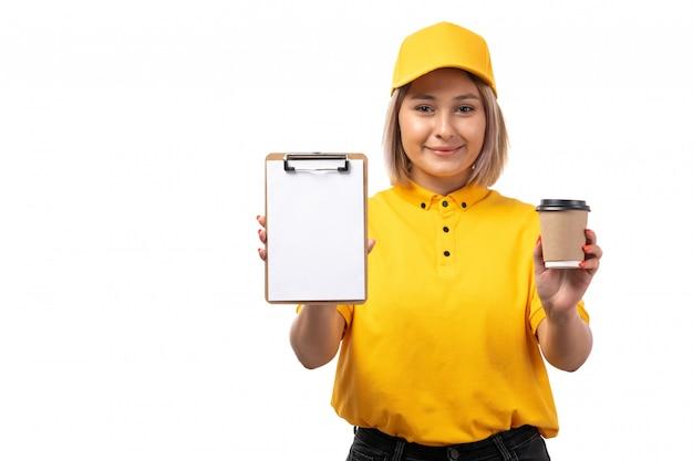 Вид спереди курьер женского пола в желтой рубашке желтый колпачок и черные джинсы, держа чашку кофе и блокнот на белом