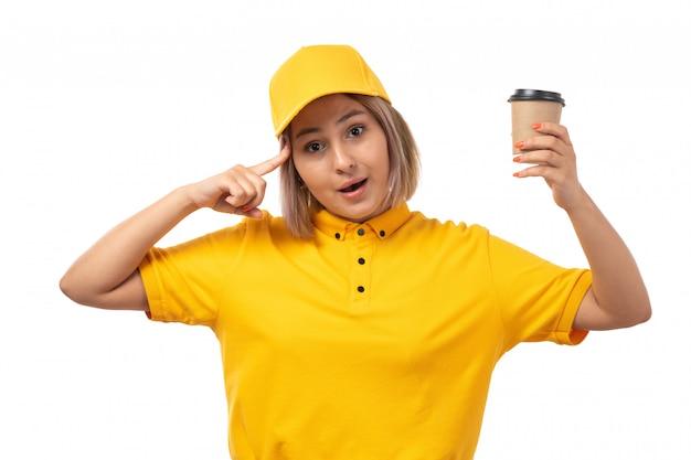 Вид спереди курьер женского пола в желтой рубашке желтой кепке и черных джинсах держит чашку кофе на белом Бесплатные Фотографии