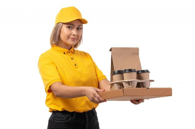 Вид спереди курьер женского пола в желтой рубашке желтой кепке и черных джинсах, держа чашки кофе и коробку с пиццей на белом