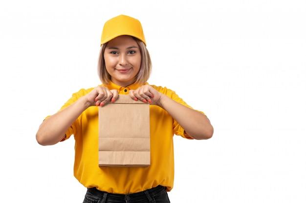 Вид спереди курьер женского пола в желтой рубашке желтой кепке и черных джинсах держит пакет еды и улыбается на белом
