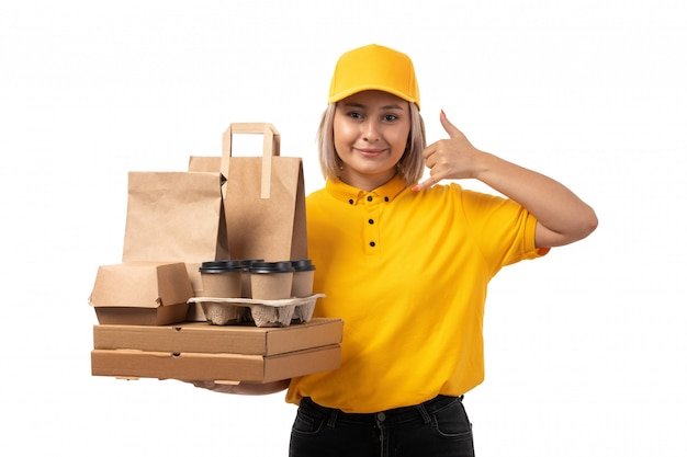 黄色のシャツイエローキャップとフードとコーヒーカップが白に笑みを浮かべてパッケージを保持している黒のジーンズで正面の女性宅配便