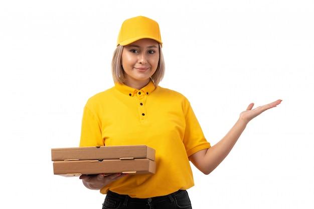 白に笑みを浮かべてピザの箱を保持している黄色のシャツイエローキャップブラックジーンズの正面図女性宅配便
