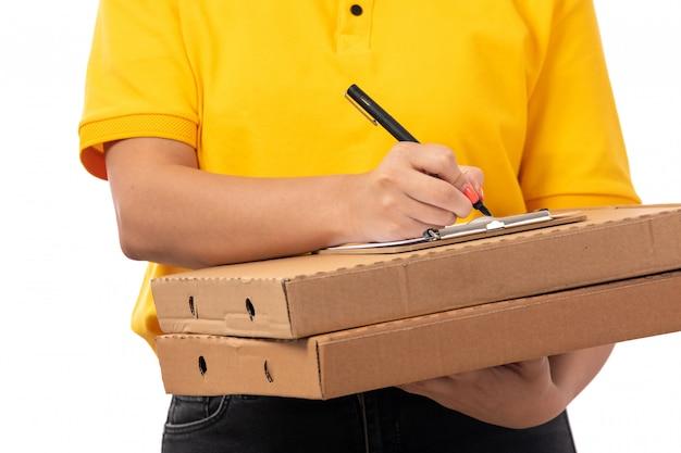 Вид спереди курьер женского пола в желтой рубашке желтой кепке и черных джинсах держит коробки для пиццы написание порядка на белом