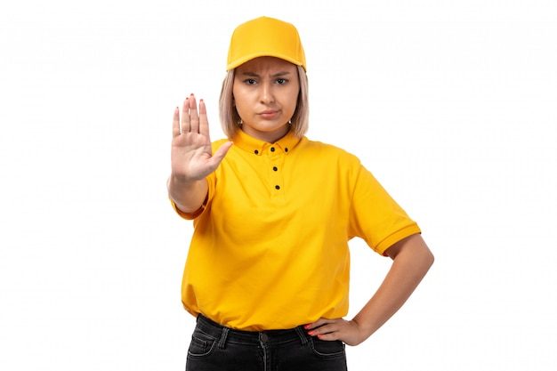 Вид спереди курьер женского пола в желтой рубашке желтой кепке и черных джинсах, показывая знак остановки на белом