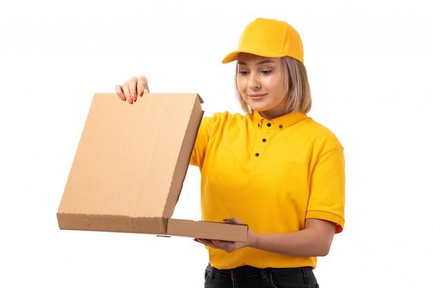 黄色いシャツの黄色い帽子と黒いジーンズが白でそれを開いて保持しているピザの箱を笑顔で正面の女性宅配便