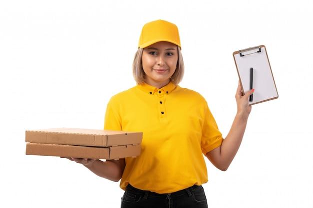 Вид спереди курьер женского пола в желтой рубашке желтой кепке черные джинсы, держа коробки для пиццы, улыбаясь на белом