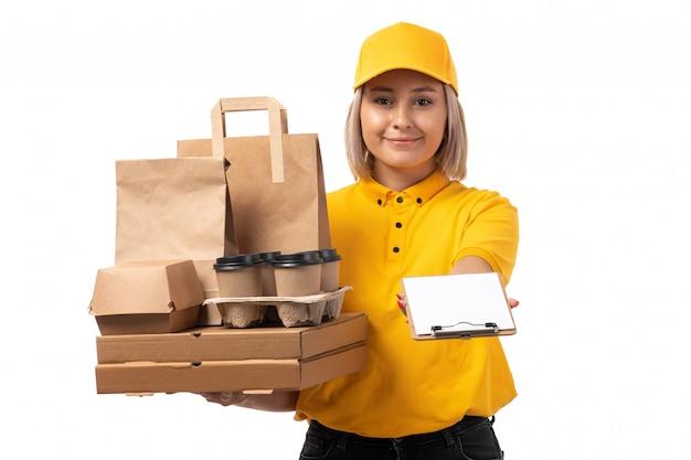 Вид спереди курьер женского пола в желтой рубашке желтой кепке черные джинсы, улыбаясь, держа коробки и кофе с бумагой на белом