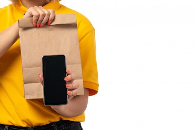 Вид спереди курьер женского пола в желтой рубашке желтой кепке черные джинсы, улыбаясь, держа смартфон и пакеты с едой на белом