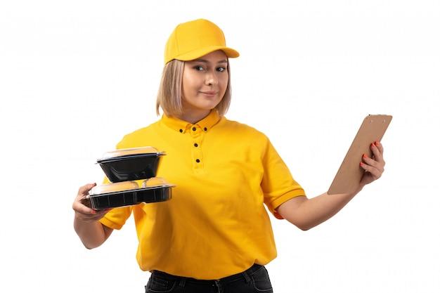 Вид спереди курьер женского пола в желтой рубашке желтой кепке, улыбаясь, держа миски с едой и бумаги на белом