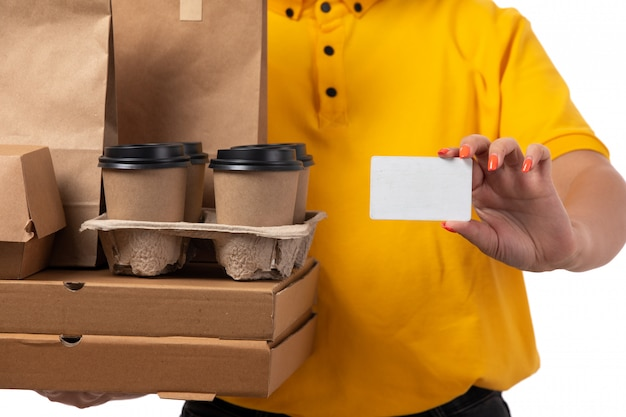黄色のシャツイエローキャップピザボックスコーヒーと白の白いカードを保持笑みを浮かべて正面女性宅配便
