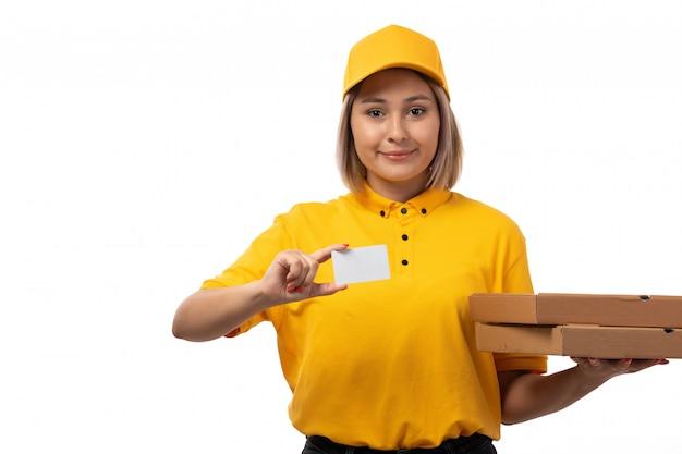 Вид спереди курьер женского пола в желтой рубашке желтой кепке, улыбаясь, держа белые карты и коробки для пиццы на белом