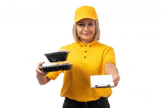 Молодая женщина-курьер, вид спереди, в желтой рубашке, желтой кепке и черных джинсах с мисками с едой и фирменным блокнотом на белой униформе