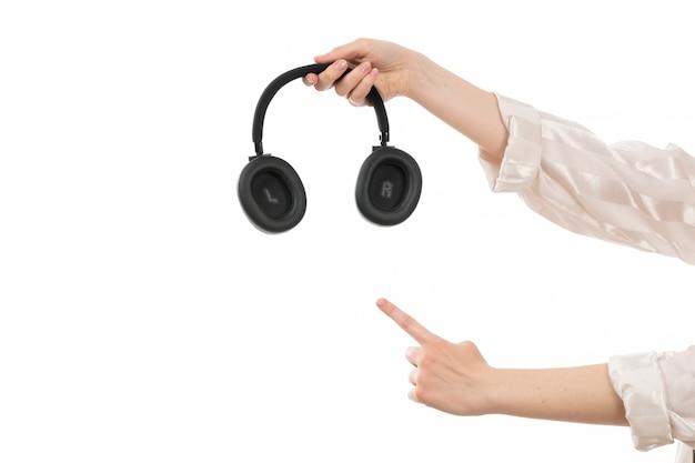 Вид спереди женская рука держит черные наушники, показывая указательный знак на белом
