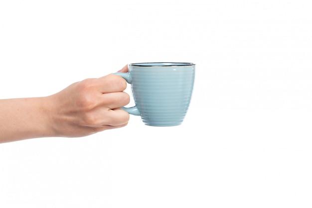 Вид спереди женская рука держит маленькую синюю чашку на белом