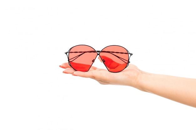 Вид спереди женская рука держит красные очки на белом