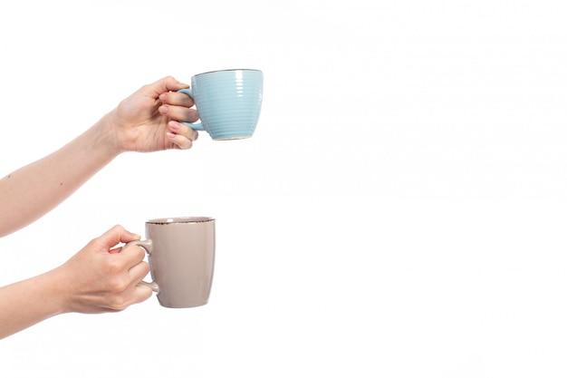 Вид спереди женские руки держат разноцветные чашки на белом