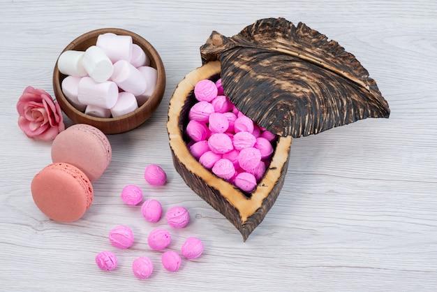 Вид спереди французские макароны вместе с зефиром и розовым, конфеты на белом, конфеты, сладкое сахарное печенье