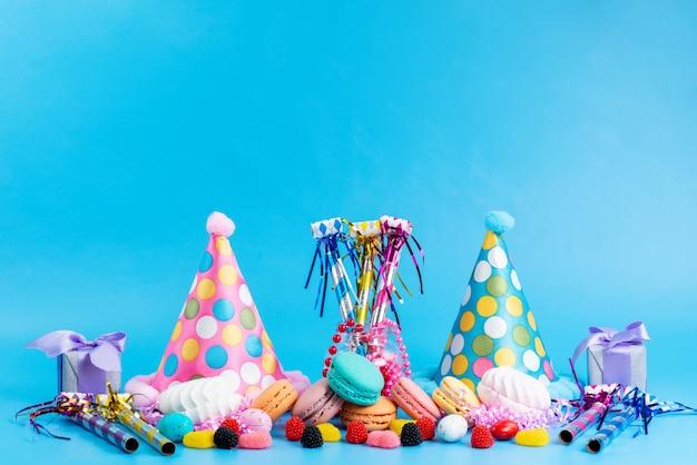 Французские макаруны, вид спереди, красочные вместе с конфетами и забавными кепками на синем фоне.