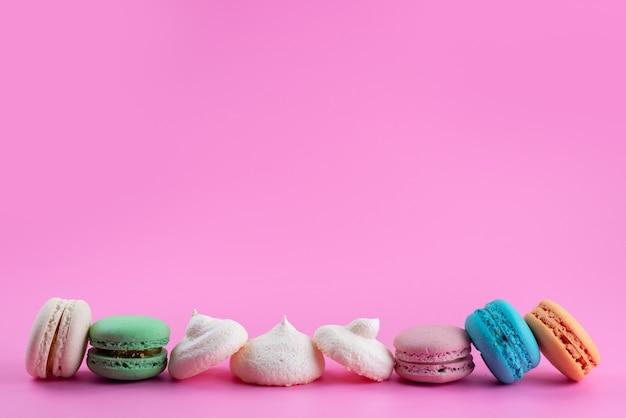 Французские макароны, вид спереди, вкусные и цветные на розовом, сахарный торт бисквитного цвета
