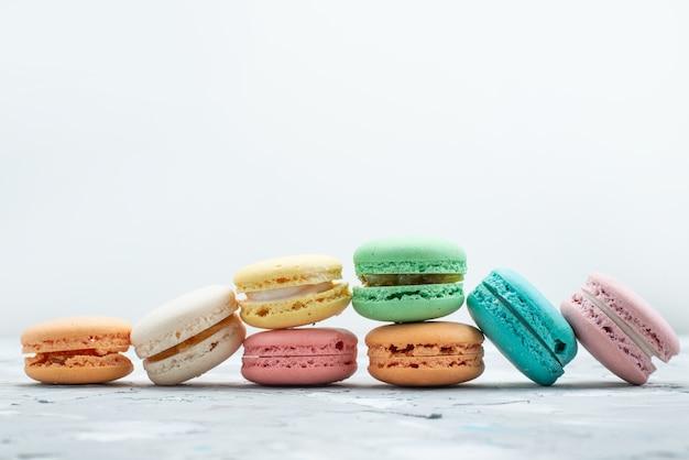 Французские макароны, вид спереди, вкусные и круглые, сформированные на белом, цвете бисквитного торта