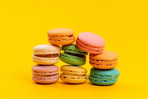 Вид спереди французские макароны вкусные круглые, изолированные на желтом, кондитерские изделия из бисквитного торта