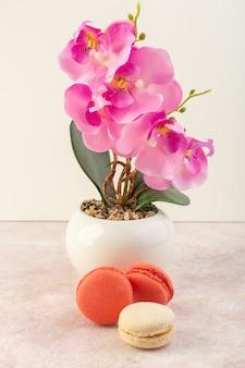 ピンクの机の上の花を持つ正面フレンチマカロン