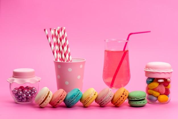 Вид спереди французские макароны с соломкой для сока и леденцами на палочке вместе с красочными конфетами на розовом, цвете кондитерских изделий из бисквитного торта