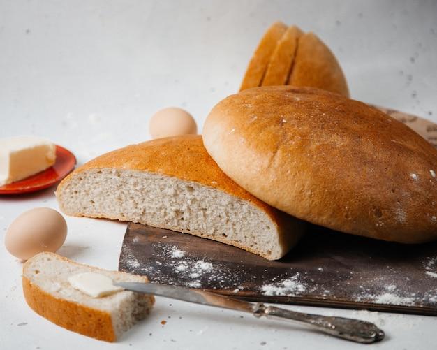 Вид спереди свежий хлеб круглый, сформированный с яйцами и цветком на белой поверхности, тесто для еды из булочки