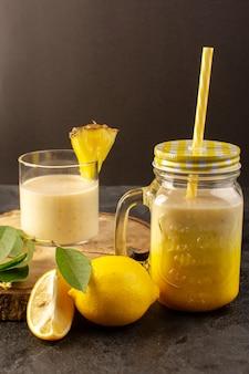 Вид спереди свежий коктейль вкусный прохладительный напиток внутри банки с соломой возле деревянного стола вместе с зелеными листьями на темном фоне пьют летний сок