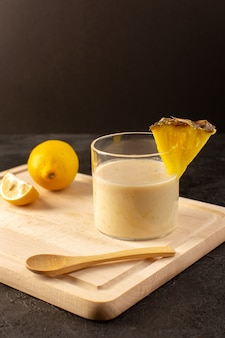 Вид спереди свежий коктейль вкусного прохладительного напитка внутри маленького стакана возле деревянного кремового стола на темном фоне напитка летнего сока