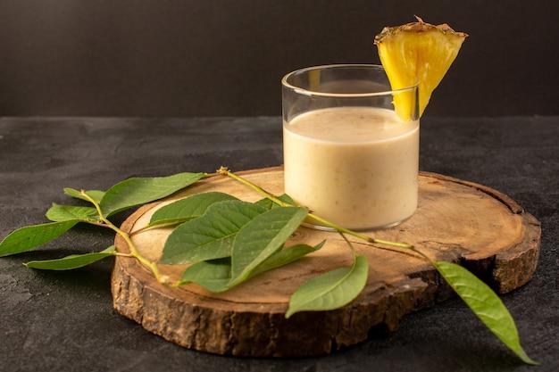 Вид спереди свежий коктейль вкусного прохладительного напитка внутри маленького стакана возле деревянного стола вместе с зелеными листьями на темном фоне напитка летнего сока