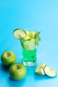Свежий фруктовый коктейль, вид спереди, с кусочками свежих фруктов, ледяное охлаждение на синем, питьевой коктейль, фруктовый цвет
